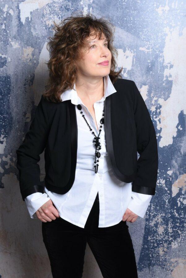 Klassische weiße Bluse mit einer kurzen schwarzen Jäckchen und einer schwarzen Kette