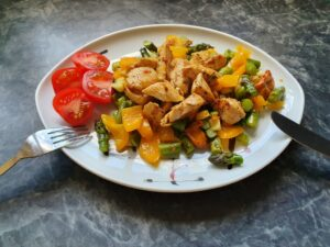 Antiaging with healthy food! Here fried vegetables with chicken strips and fresh tomato