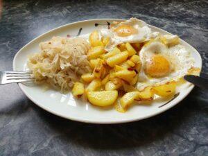 Anti-Aging mit der richtigen Ernährung! Hier: Bratkartoffeln mit 2 Spiegeleiern und frischem Sauerkraut Salat. Dabei Sauerkraut sollte nicht gekocht werden, sondern direkt aus dem Fass/Packung zubereitet.